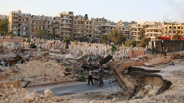 People walk near an over-crowded graveyard in the rebel-held al-Shaar neighborhood of Aleppo, Syria.