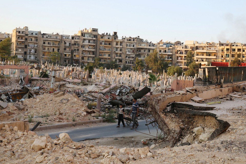 People walk near an over-crowded graveyard in the rebel-held al-Shaar neighborhood of Aleppo, Syria.
