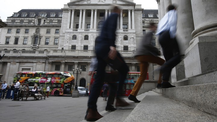 Pedestrians walk past the Bank of England