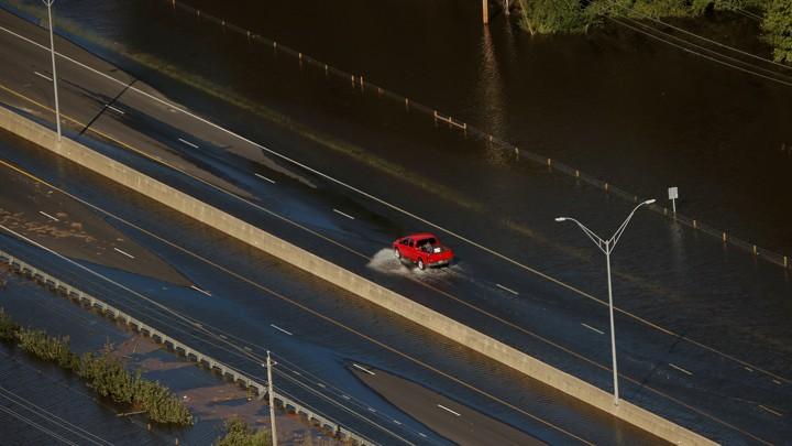A car drives through flood waters along Interstate 95 after Hurricane Matthew hit Lumberton, North Carolina.