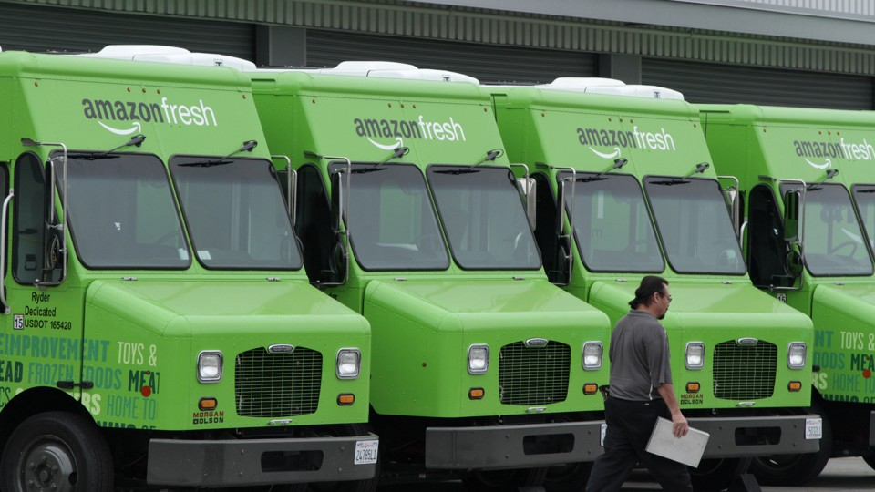Amazon Fresh delivery vans are lined up outside an Amazon warehouse
