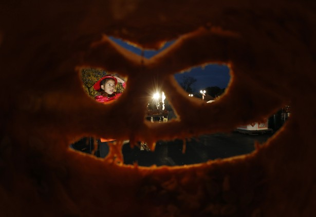 A girl is seen through one of the thousands of carved pumpkins at an Illinois pumpkin festival in 2013.
