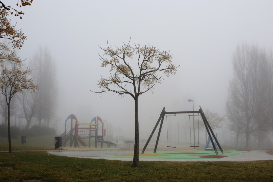 Fog surrounds an empty playground.