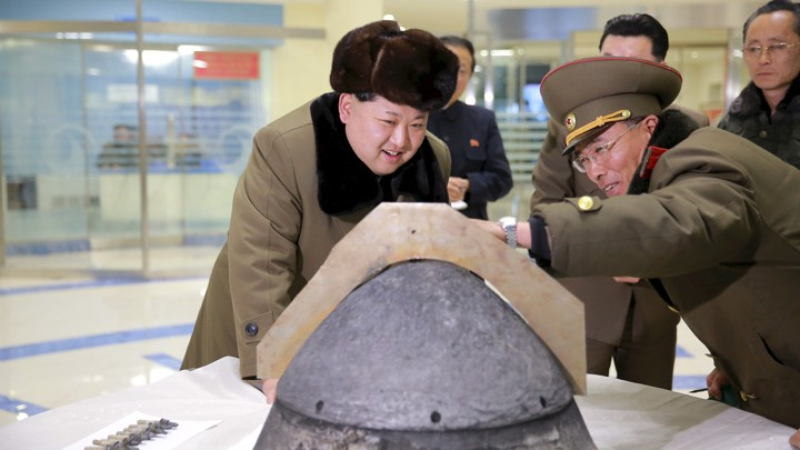 North Korean leader Kim Jong Un looks at a rocket warhead tip after a simulated test of atmospheric re-entry of a ballistic missile