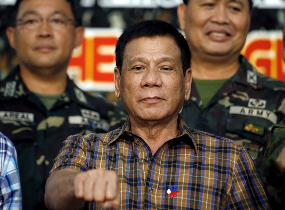 """Philippine President Rodrigo Duterte makes a """"fist bump"""", his May presidential elections campaign gesture, with soldiers during a visit at Capinpin military camp in Tanay, Rizal in the Philippines August 24"""