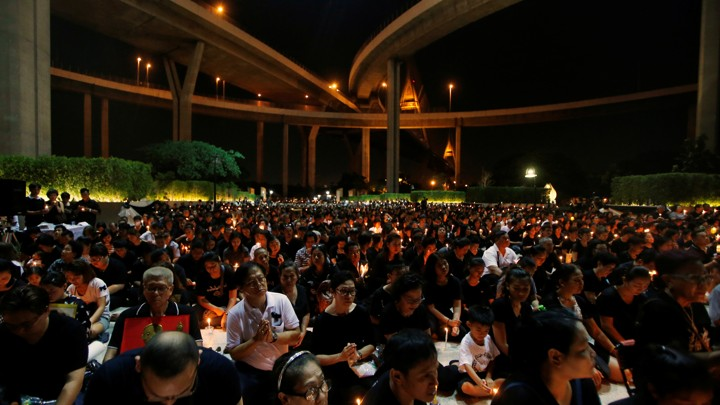 People pay their respect to the late King Bhumibol Adulyadej during a candlelight vigil at Lat Pho Park in Song Khanong, Thailand October 19, 2016.