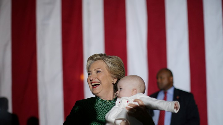 Hillary Clinton holds a baby after attending a campaign rally in Charlotte, North Carolina on October 23, 2016.