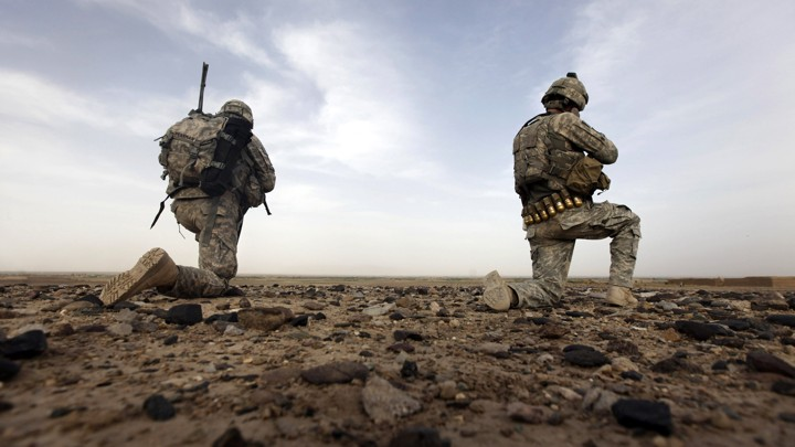 Two soldiers kneel on the ground in Afghanistan.