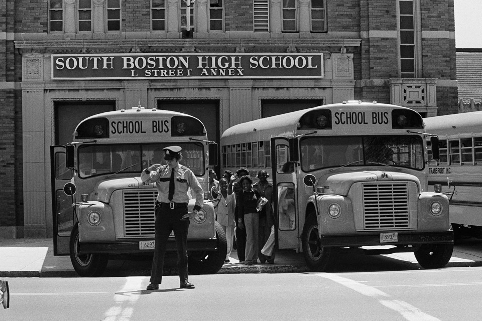 In a black-and-white photo from 1975, black students board school buses lined up in front of South Boston High School. A police office stands in front of one of the busses.