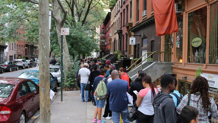 A long line of students and parents tumbles onto the New York City sidewalk.