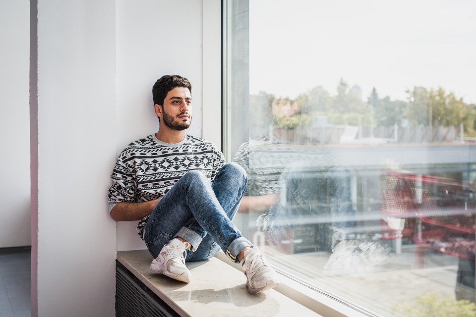 A young man sits on a ledge inside a building with a giant window.