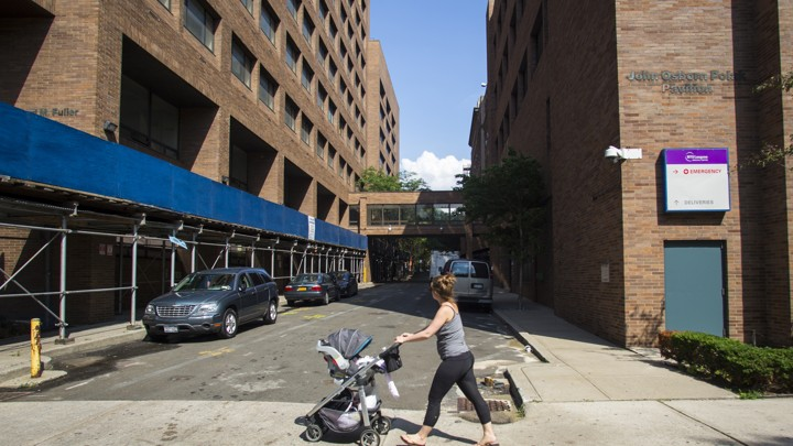 A young woman pushes a stroller past Long Island College Hospital in Brooklyn, New York.