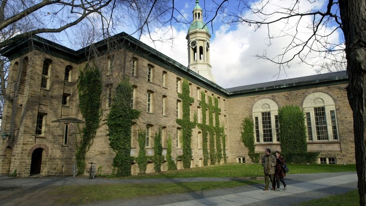 Two people walk past a brick, ivy-covered building on the Princeton University campus.