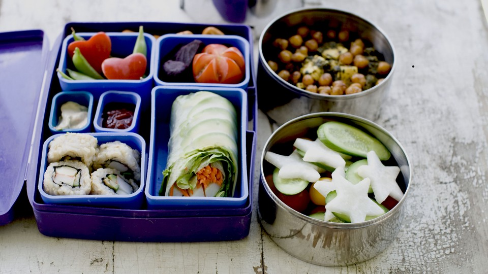 A lunch box filled with sushi and vegetables.