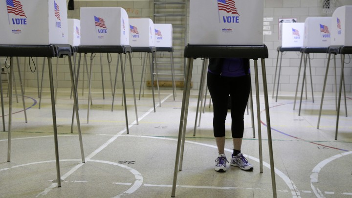 A woman votes in a voting booth at a school