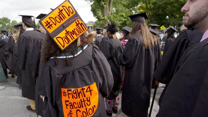 "A student at graduation wears a cap that reads ""Don't Do Dartmouth."" The gown reads ""Fight 4 Faculty of Color."""