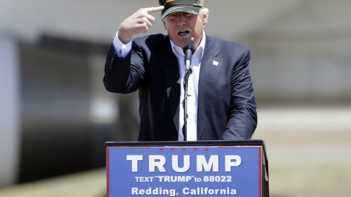 "Republican presidential candidate Donald Trump gestures to a his camouflaged ""Make America Great"" hat at a campaign rally at the Redding Municipal Airport in Redding, Calif."