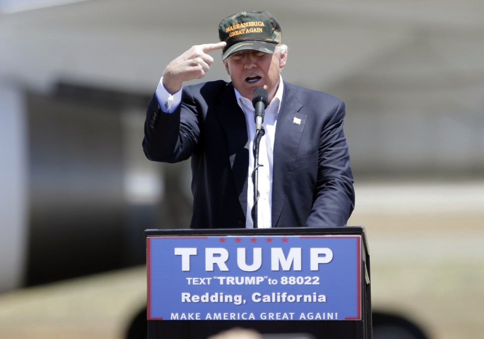 """Republican presidential candidate Donald Trump gestures to a his camouflaged """"Make America Great"""" hat at a campaign rally at the Redding Municipal Airport in Redding, Calif."""
