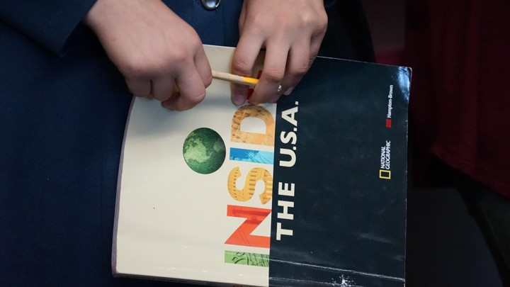 "A student's hands hold a pencil in front of a book whose cover reads ""Inside the USA"""