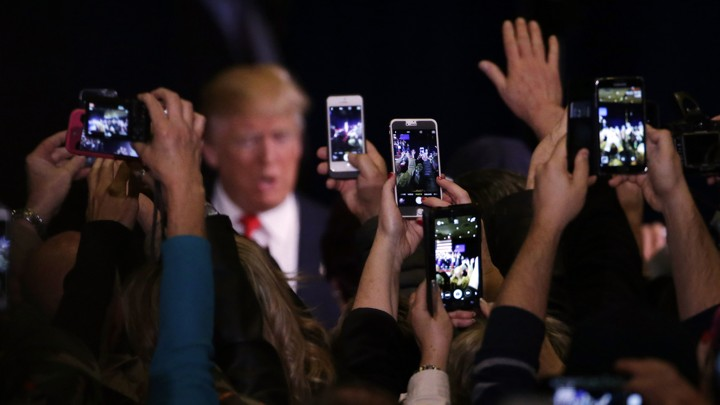 Donald Trump's supporters take cell phone photographs of him during a February 2016 rally in Reno, Nevada.