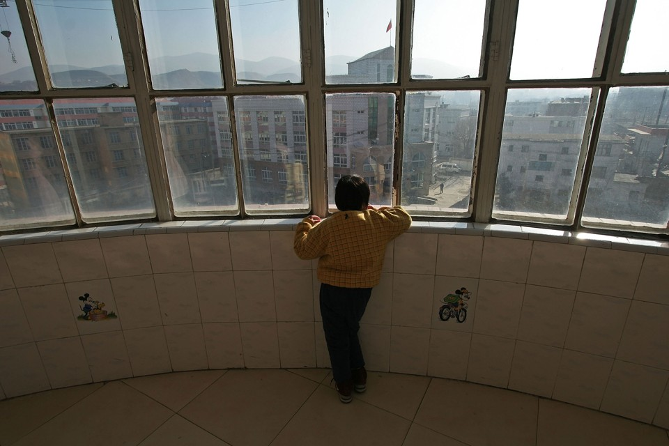 A child with autism looks out a window at the Xining Orphan and Disabled Children Welfare Center, in China.