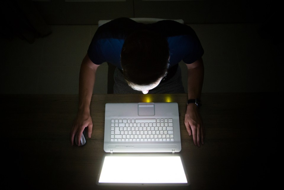 A man on his computer in a dark room