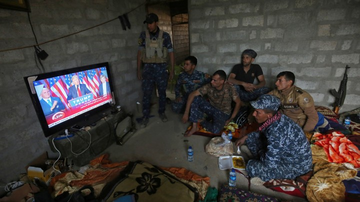 Members of the Iraqi forces watch Donald Trump giving a speech after he won the U.S. president election.