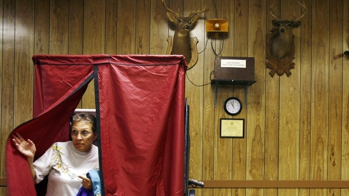 A woman leaves a voting booth with a blue curtain, set in front of hunting trophies, in Danielsville, Pennsylvania