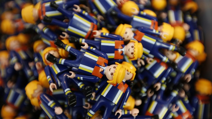 A sea of Playmobil figurines dressed in navy blue suits fills the frame.