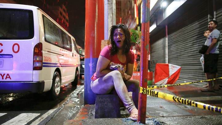 A woman cries after her husband was shot dead by unidentified gunmen riding motorcycles in Manila.