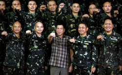 "Philippine President Rodrigo Duterte makes a ""fist bump"", his May presidential elections campaign gesture, with soldiers during a visit at Capinpin military camp in Tanay, Rizal in the Philippines August 24, 2016."