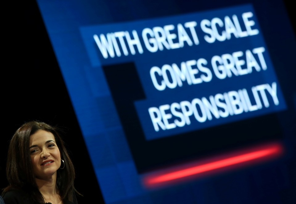 "Sheryl Sandberg grimaces in front of a large slide that says ""WITH GREAT SCALE COMES GREAT RESPONSIBILITY."""
