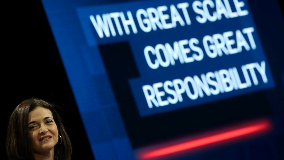 """Sheryl Sandberg grimaces in front of a large slide that says """"WITH GREAT SCALE COMES GREAT RESPONSIBILITY."""""""