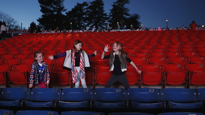 Three girls dance in a stadium full of blue and red chairs as they wait for a Hillary Clinton rally to begin in Philadelphia on Saturday.