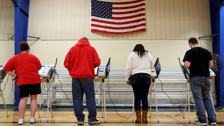 The backs of voters as they cast their ballots. They stand underneath an American flag, presumably in a gymnasium.