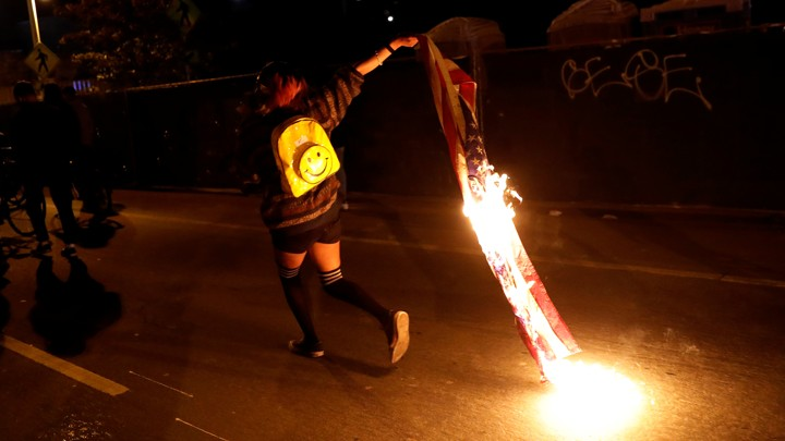 A demonstrator burns an American flag to protest the election of Donald Trump on November 10 in Oakland, Calif.