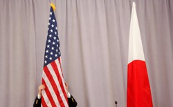A worker adjusts the U.S. flag before Japanese Prime Minister Shinzo Abe addresses media following a meeting with President-elect Donald Trump in New York City on November 17, 2016.