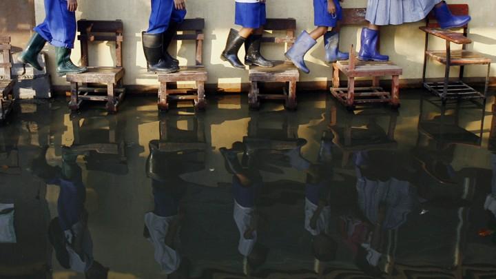 Students wearing rain boots walk on desks across their flooded classroom.