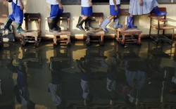 Students wearing rain boots walk on desks across their flooded classroom.