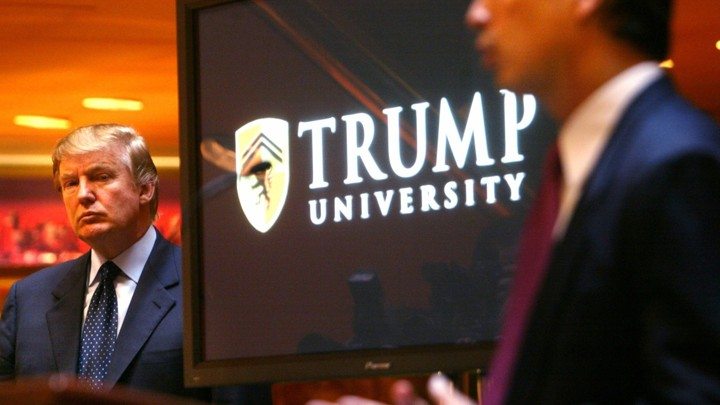 "Donald Trump stands next to a screen that reads ""Trump University."""