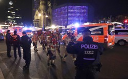 Firefighters walk past ambulances after a truck ran into a crowded Christmas market and killed several people in Berlin on December 19, 2016.