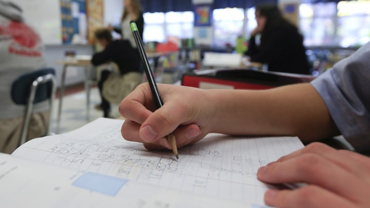 A student writes with pencil on a sheet of notebook paper.