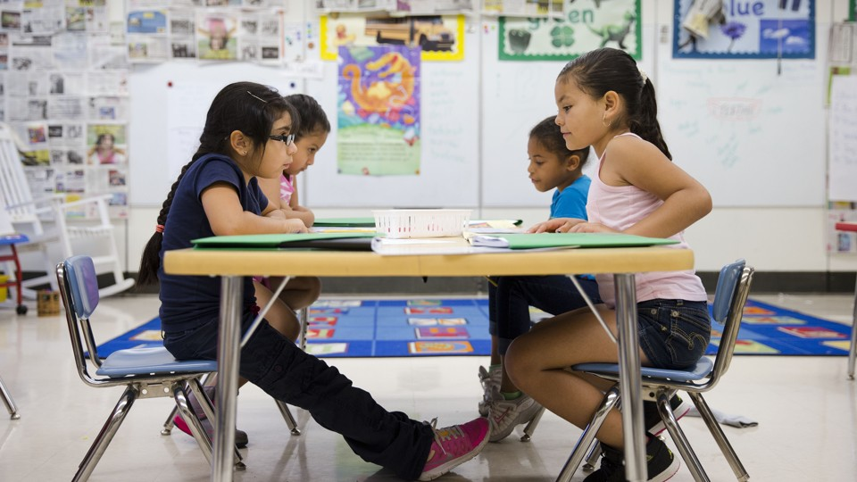 Hispanic kindergartners sit at a desk in a classroom in Kennett Square, Pennsylvania