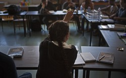A student's back is photographed as she raises her hand. She wears her hair in long pigtail braids.