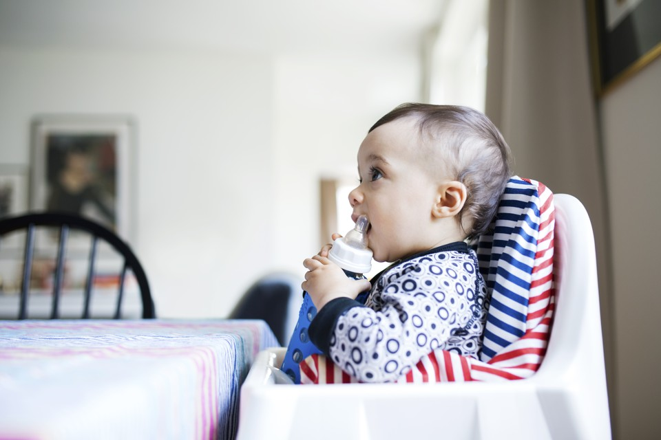 A baby sits in a high chair holding a bottle.