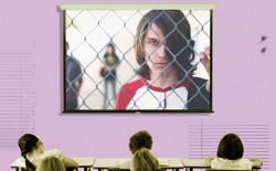 "A frame from the documentary ""Bad Kids"" fills the screen of a projector in a classroom."