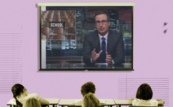 "A projector screen is filled with a screengrab from John Oliver's show. The word ""school"" appears behind Oliver."
