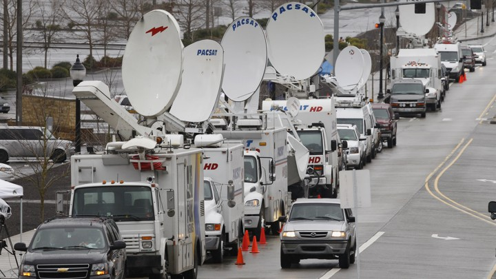 Television satellite trucks line an Oregon roadway near the scene of a mall shooting in 2012.