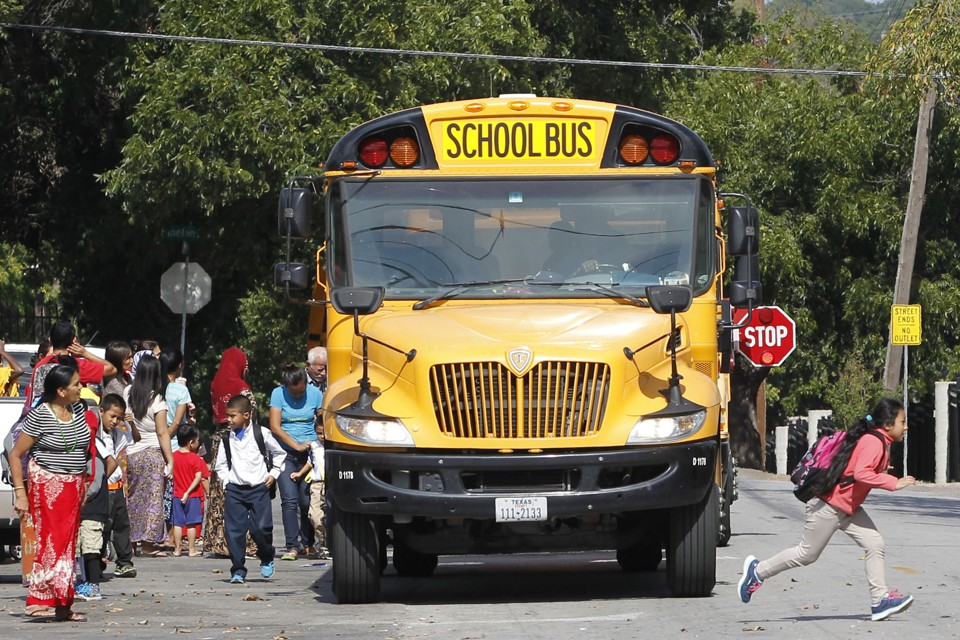 The front of a school bus fills most of the frame, as children and parents with backpacks mill about around the front of the bus. The stop sign is out on the side of the bus.