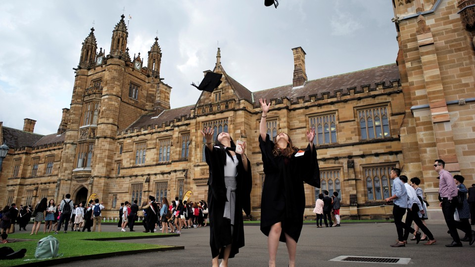 Two graduates toss their caps in the air while standing in front of a stately brick building.